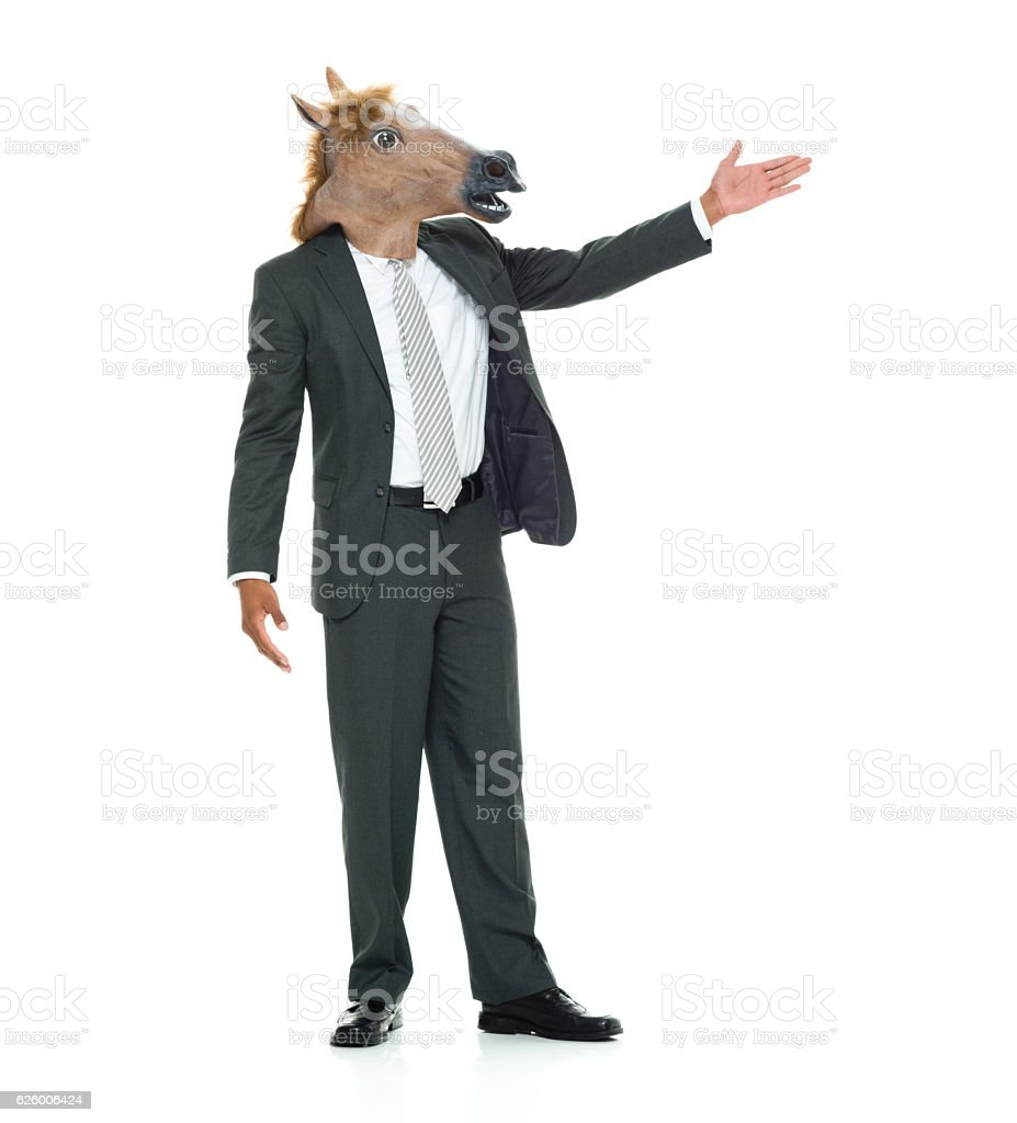 Businessman in horse costume and presenting stock photo