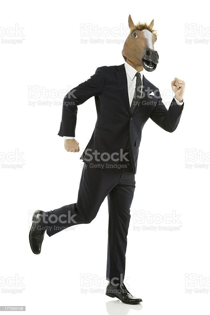 Businessman in horse mask running royalty-free stock photo