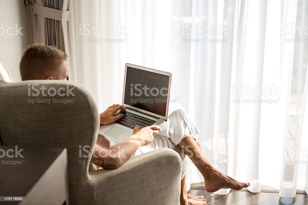 Businessman in hotel room working on laptop stock photo
