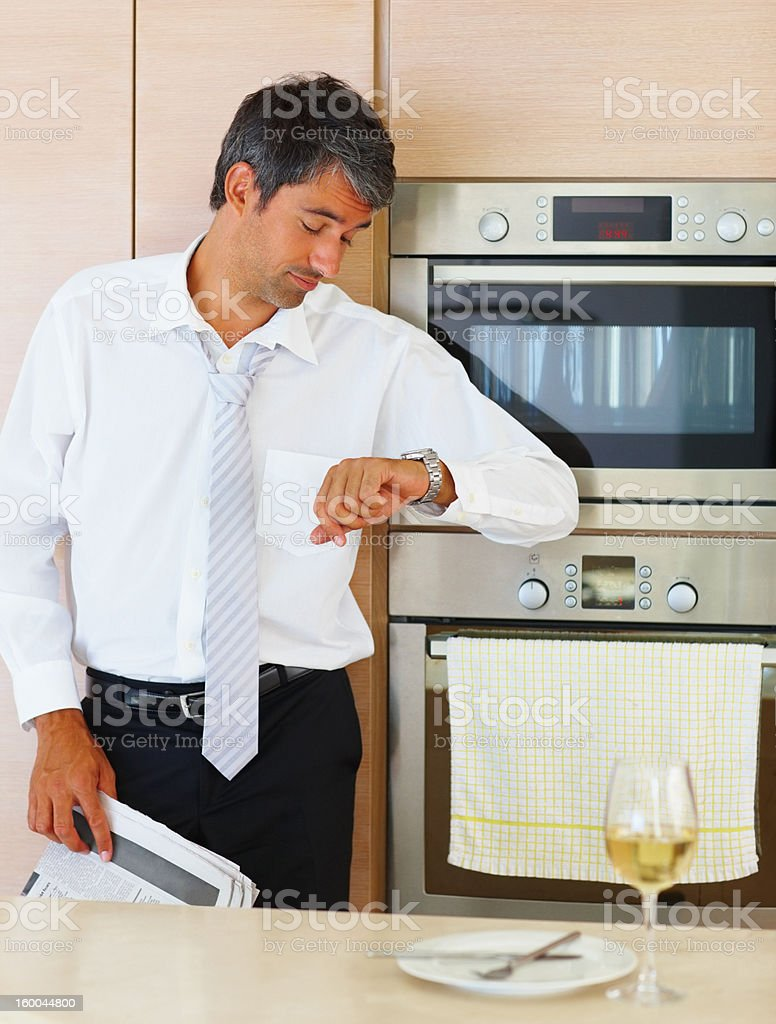 Businessman in kitchen looking at his wristwatch royalty-free stock photo