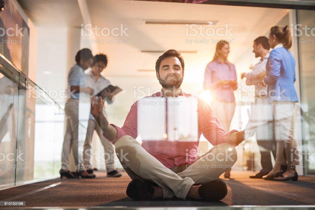 Businessman in lotus position meditating in hallway with eyes closed. stock photo