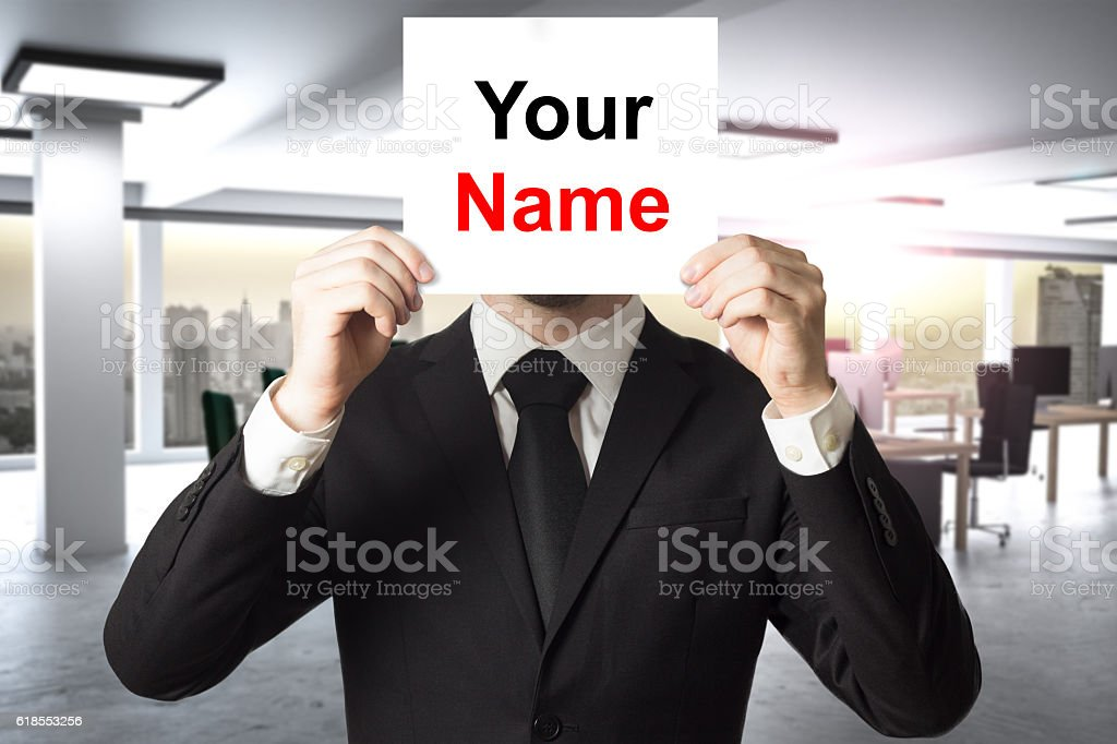 businessman in modern office hiding face behind sign your name stock photo