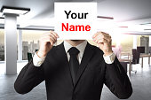 businessman in modern office hiding face behind sign your name