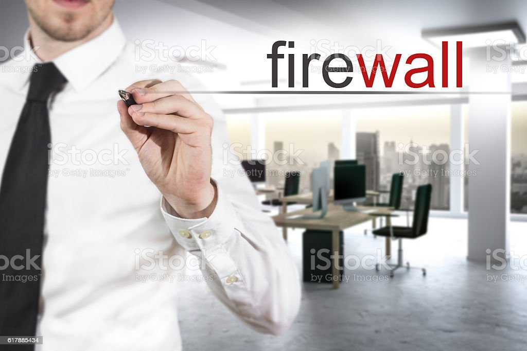 businessman in modern office writing firewall stock photo