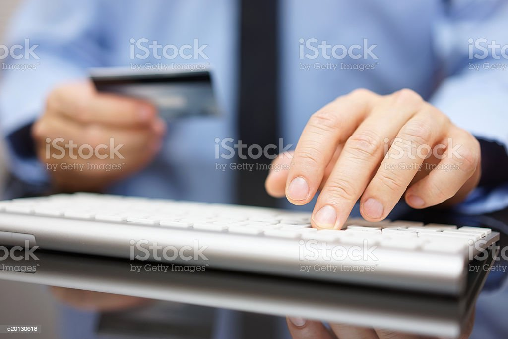 businessman in office is making bank transfer with credit card stock photo