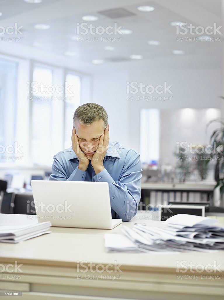 Businessman in office looking at laptop royalty-free stock photo
