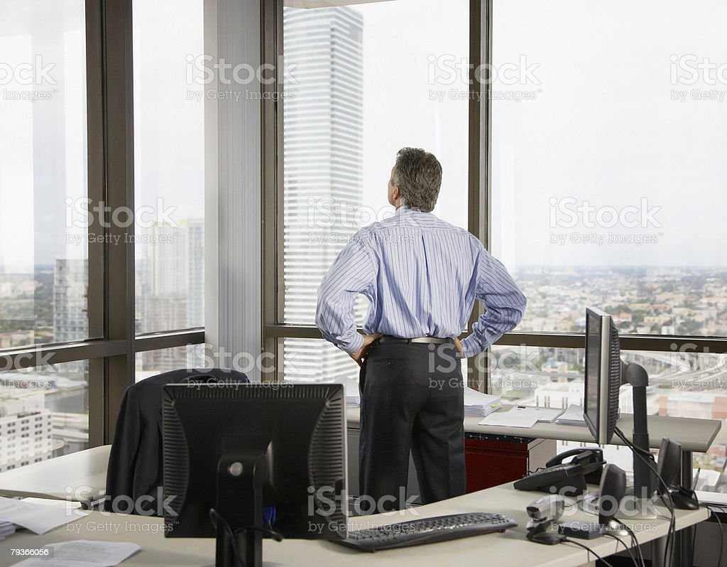 Businessman in office looking out large windows royalty-free stock photo