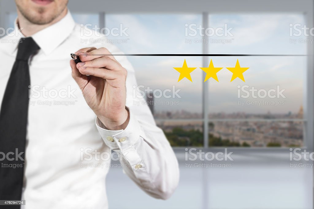 businessman in office pushing button three golden rating stars stock photo