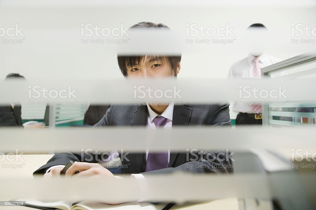 Businessman in office, view through window blinds stock photo