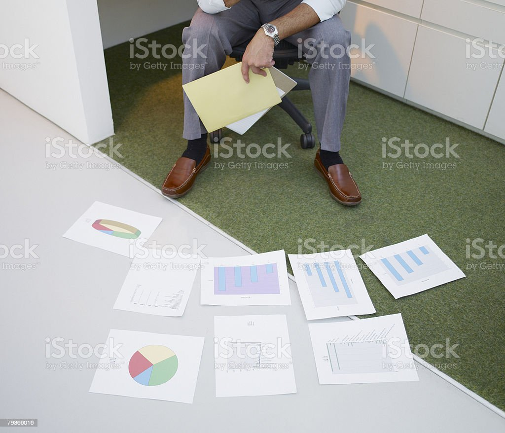 Businessman in office with charts on the floor stock photo
