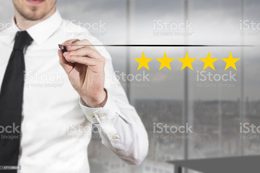 businessman in office writing five golden stars stock photo