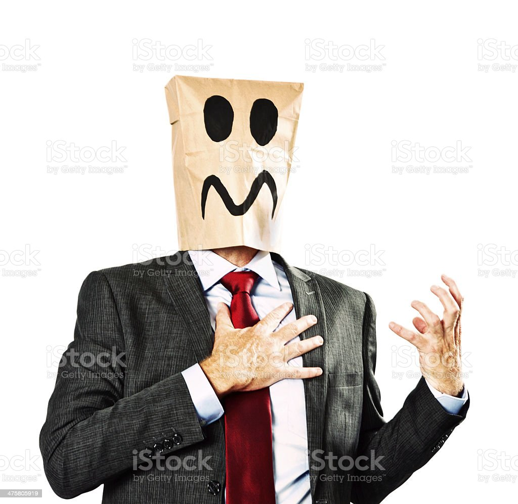 Businessman in paper-bag mask clutches chest. Miserable or heart attack? stock photo