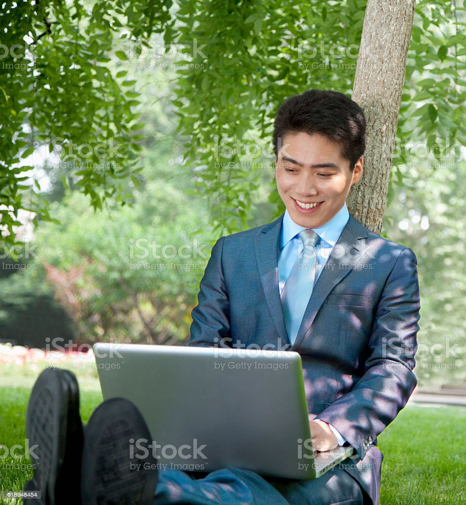 Businessman in park with laptop stock photo