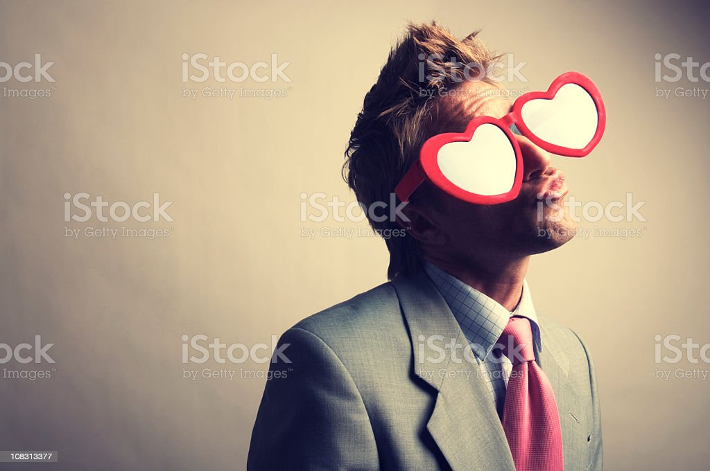 Businessman in Red Heart Glasses Kissing with Puckered Lips stock photo