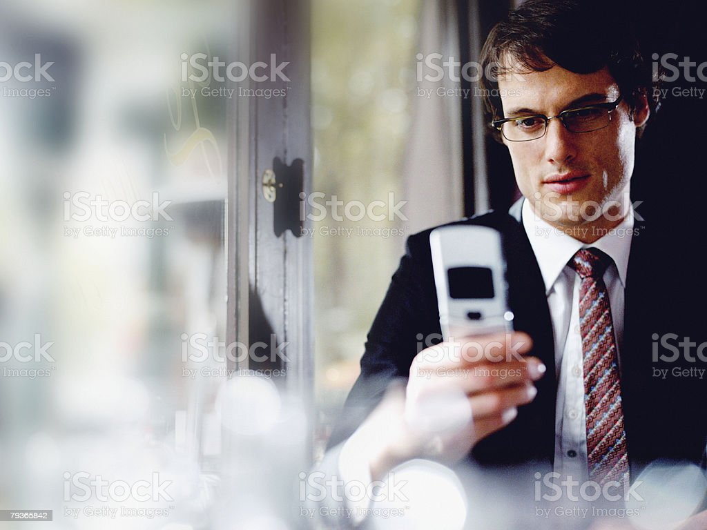 Businessman in restaurant looking at his mobile phone royalty-free stock photo