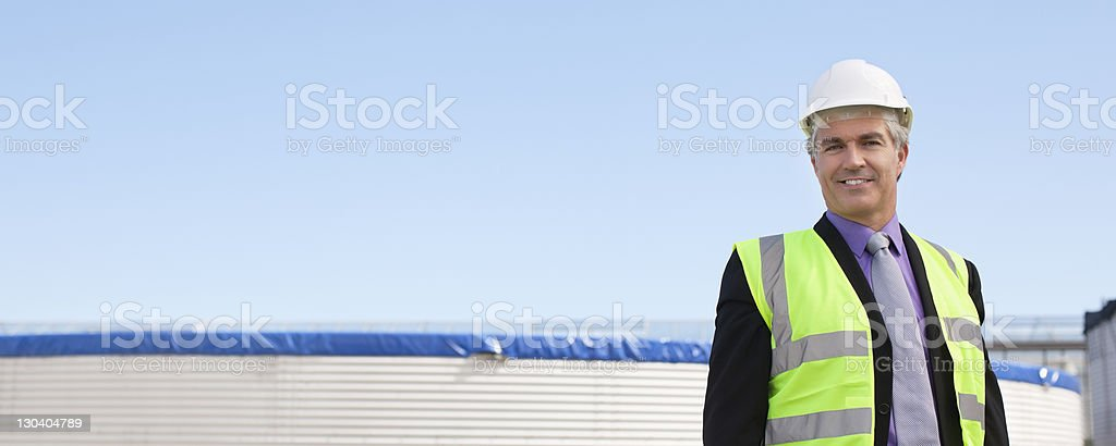 Businessman in safety gear standing outdoors royalty-free stock photo