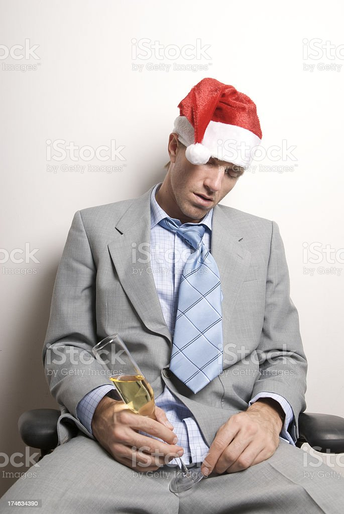 Businessman in Santa Hat Sits Drunk at Holiday Office Party royalty-free stock photo