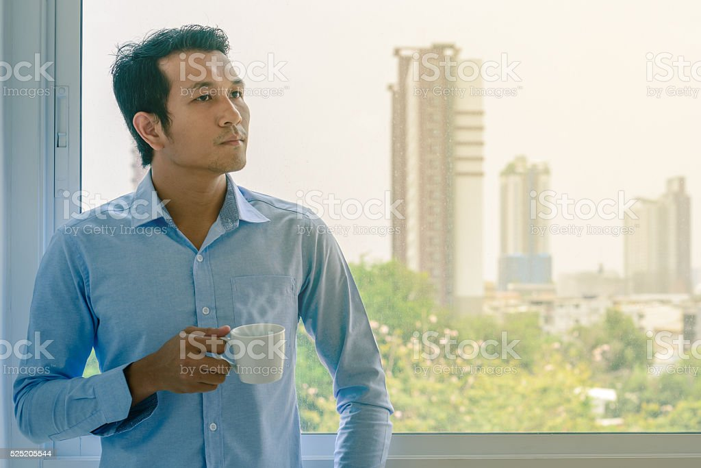 Businessman in shirt drinking hot coffee by window. stock photo