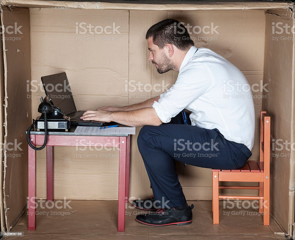 businessman in small office working on laptop stock photo