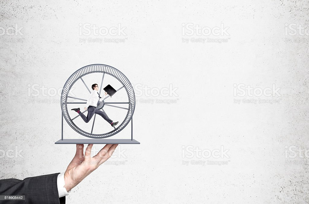 Businessman in spinning wheel stock photo