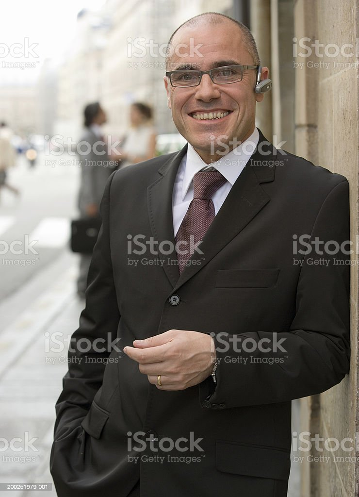 Businessman in street wearing mobile phone earpiece, smiling royalty-free stock photo