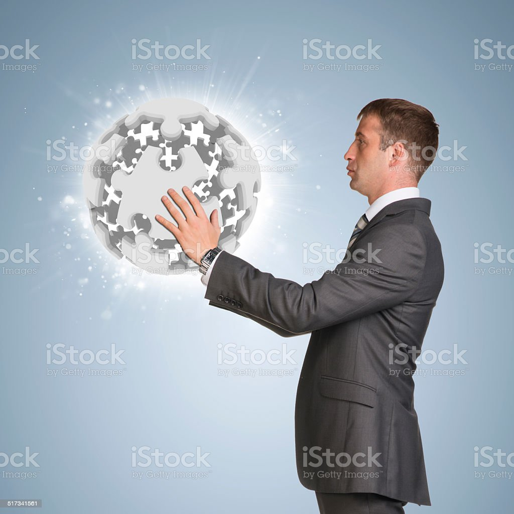 Businessman in suit hold and jigsaw puzzle sphere stock photo