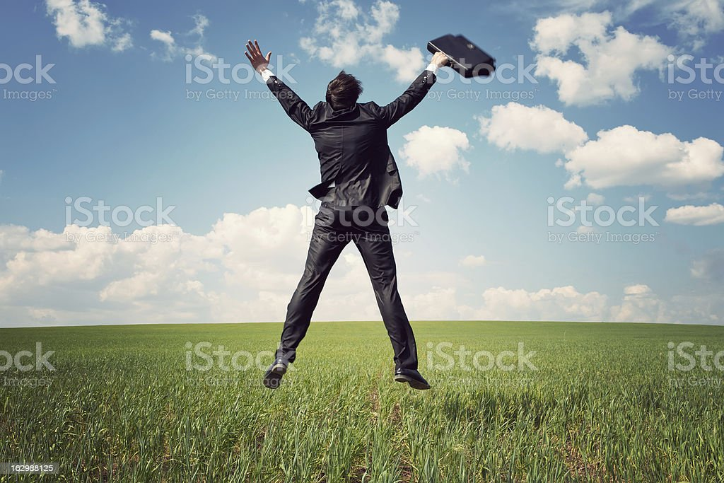 businessman in suit jumping field and holding the bag royalty-free stock photo