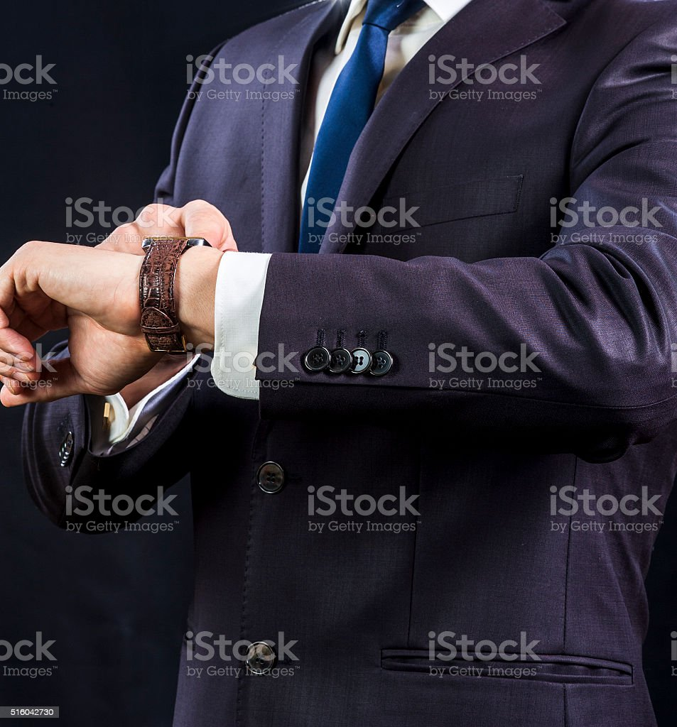 Businessman in suit looking at his watch stock photo