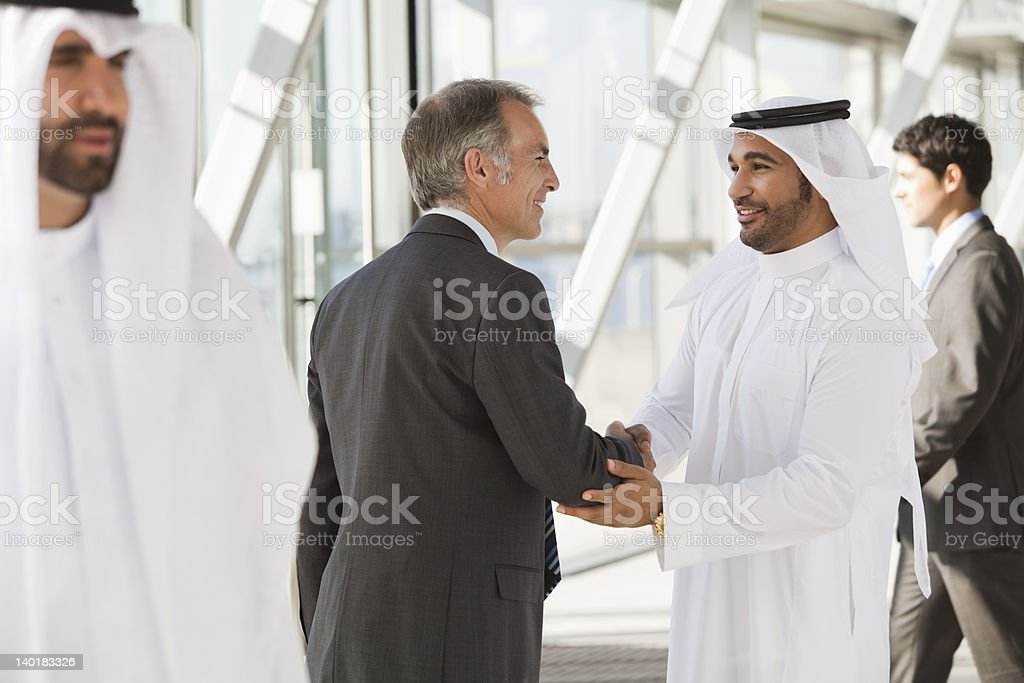 Businessman in suit shaking hands with businessman in kaffiyeh royalty-free stock photo