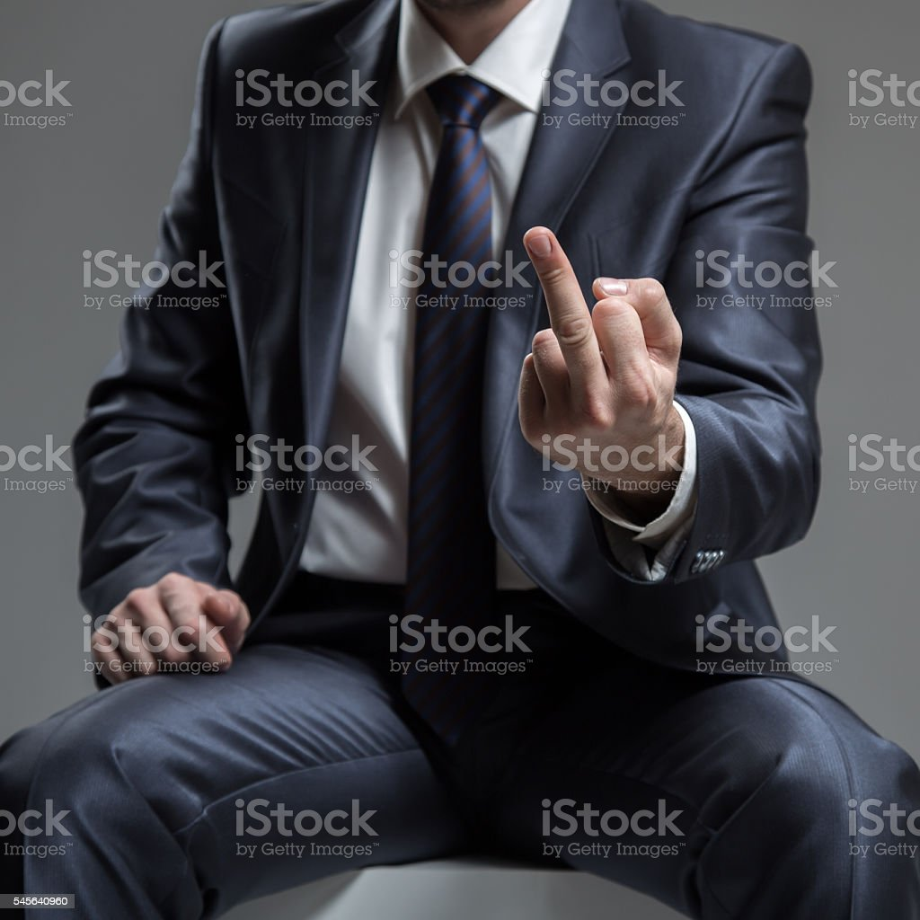 Businessman in Suit Show Middle Finger or Fuck You Sign. stock photo