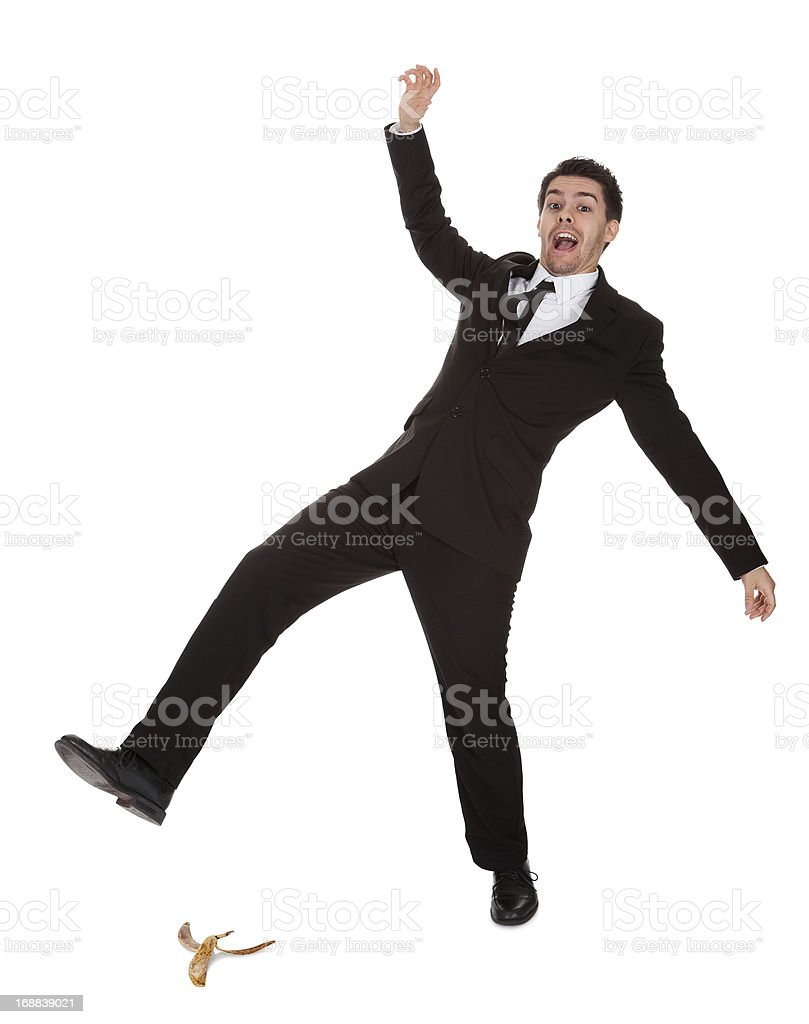Businessman in suit slipping on banana peel stock photo