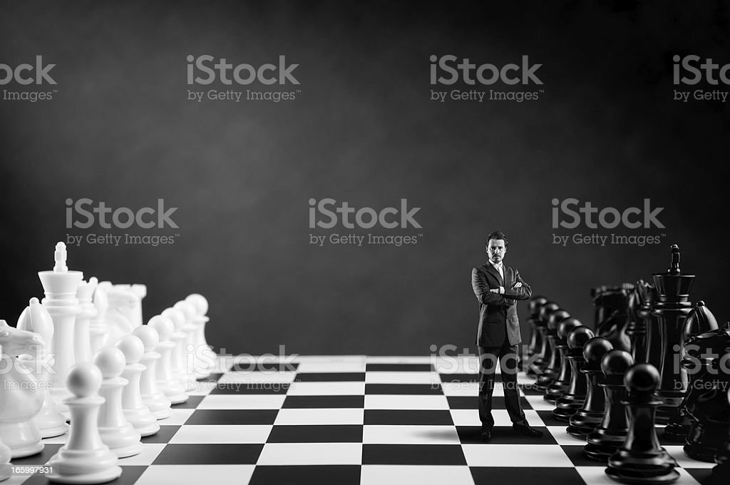 Businessman in suit standing on Chess Board near Chess Pieces royalty-free stock photo