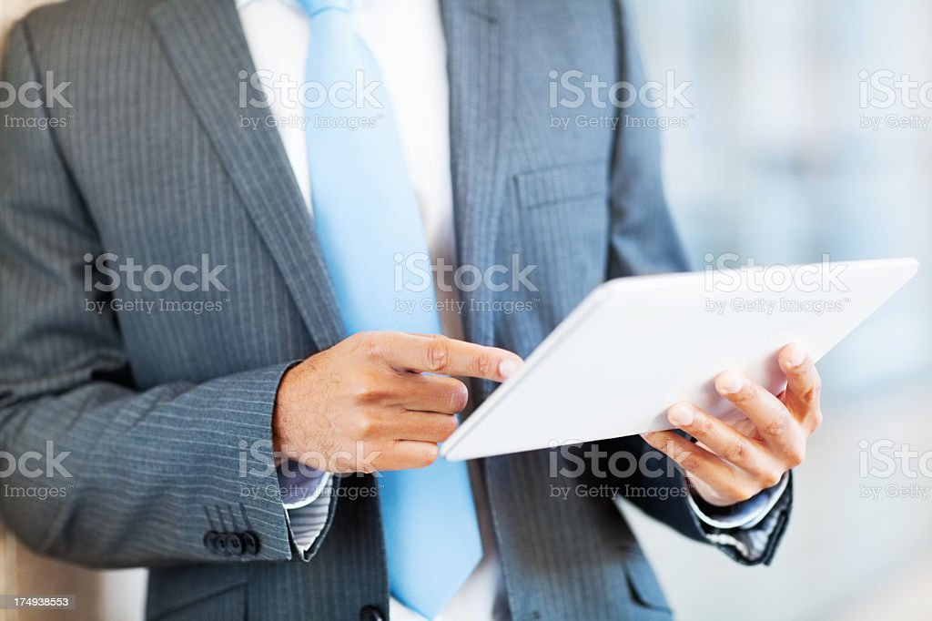 Businessman in suit using a tablet royalty-free stock photo
