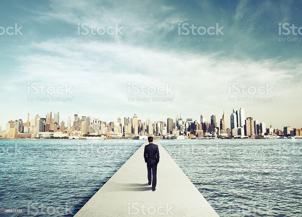 businessman in suit walking on concrete bridg stock photo