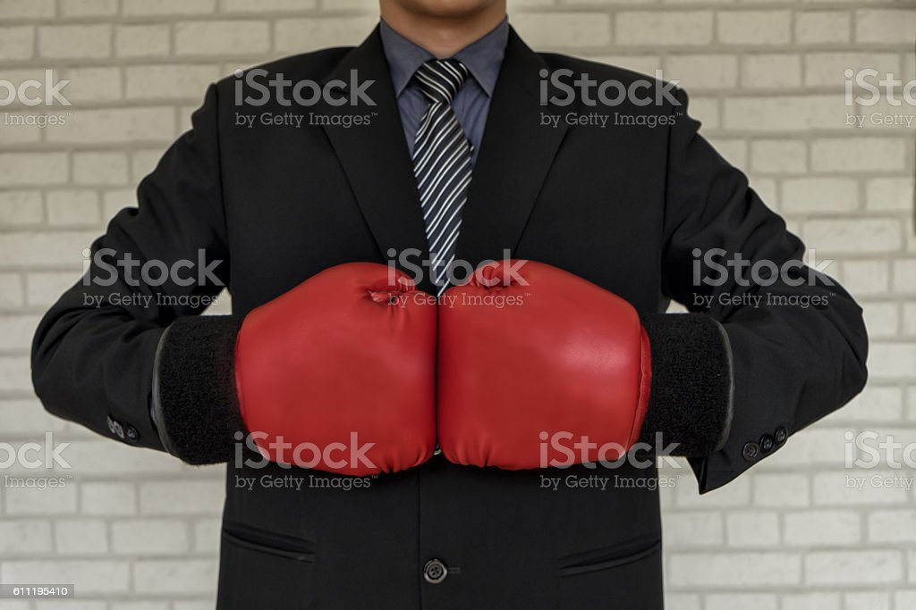 Businessman in suit with with boxing gloves, tough competitive b stock photo