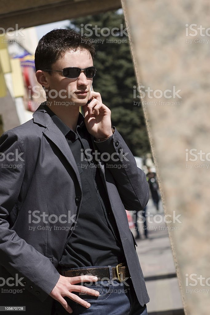 Businessman in sunglasses talks on mobile phone royalty-free stock photo