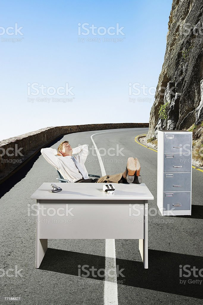 A businessman in the middle of the road at his desk royalty-free stock photo
