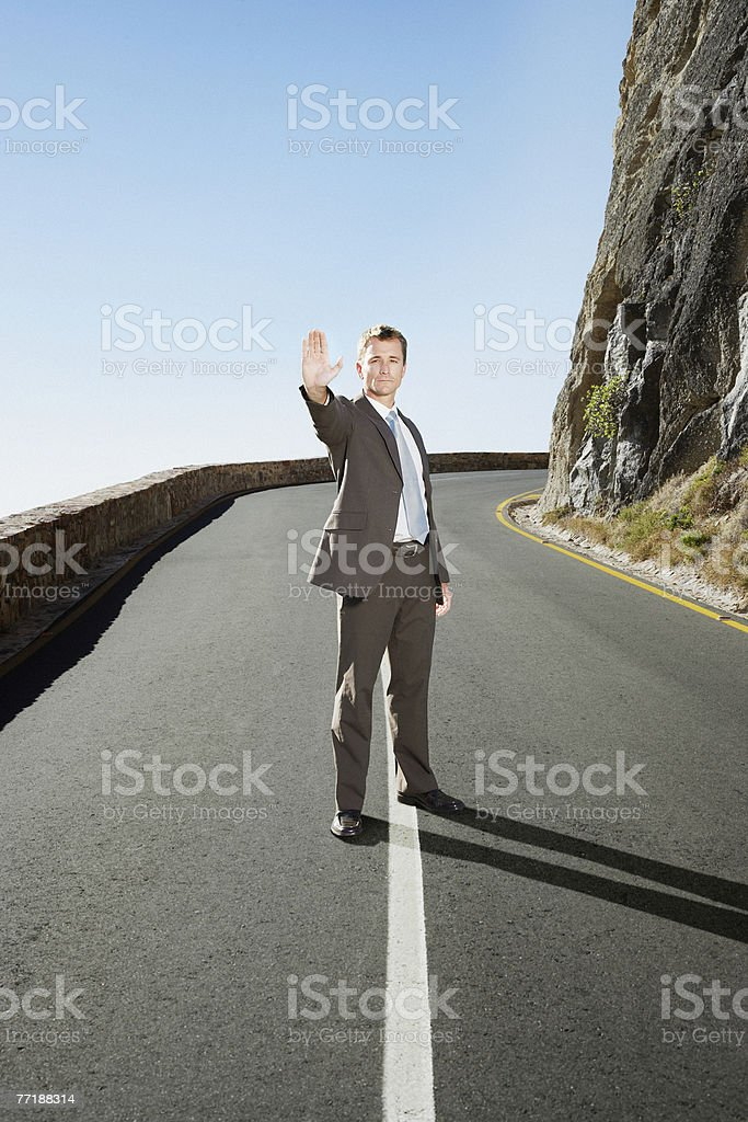 A businessman in the middle of the road stopping traffic royalty-free stock photo