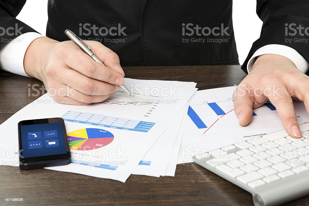 businessman in the office of table with graphics and phone royalty-free stock photo