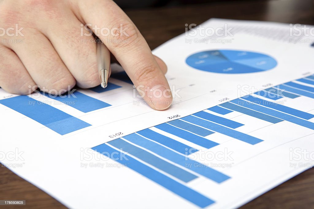 businessman in the office points to graphics royalty-free stock photo