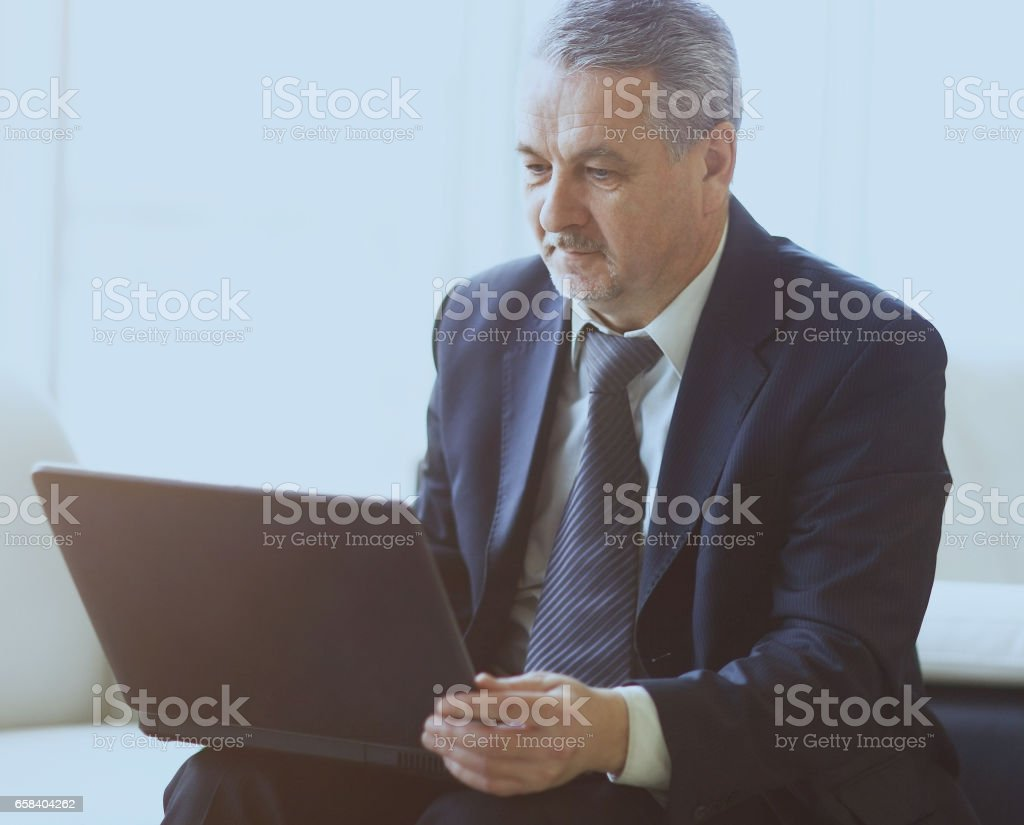 businessman in the office with laptop sits and works stock photo