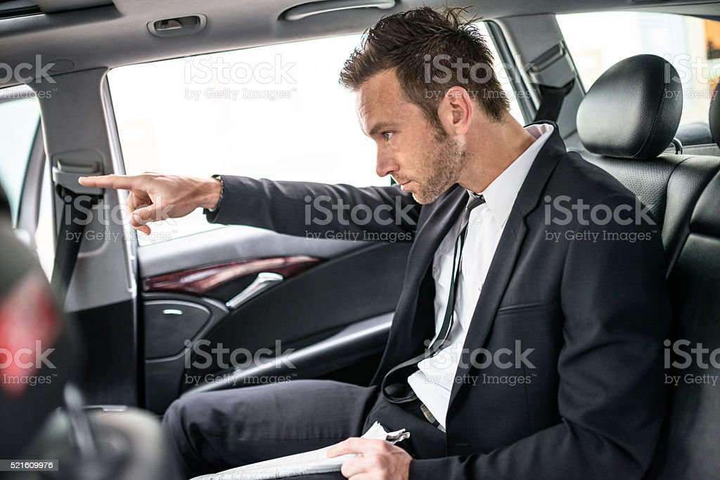 businessman in the taxi car showing the route stock photo