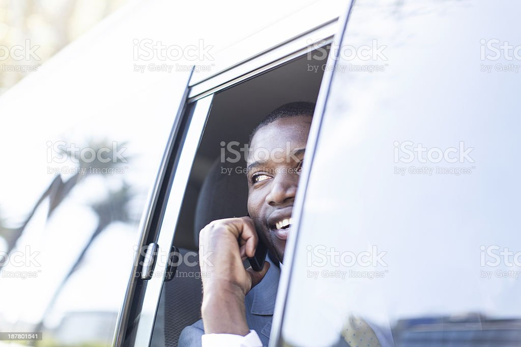 Businessman in the taxi on his cell phone stock photo