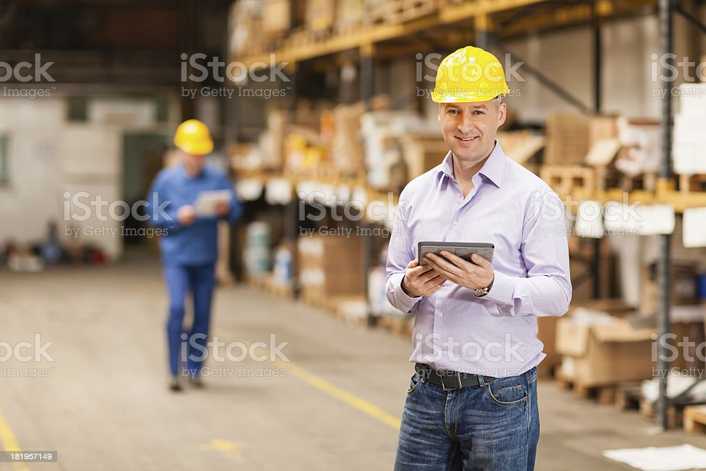 Businessman in warehouse using digital tablet royalty-free stock photo