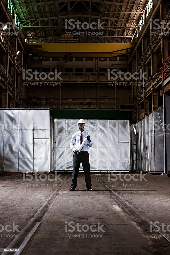 Businessman in warehouse with blueprint and hard hat stock photo