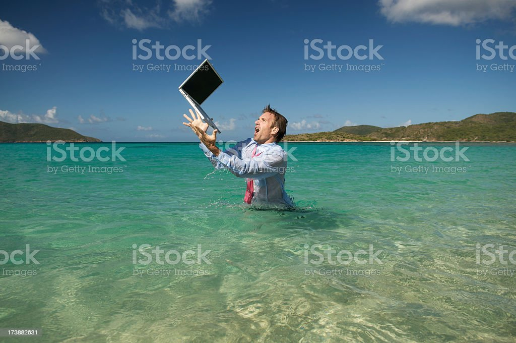 Businessman in Water Reaches for Falling Laptop royalty-free stock photo