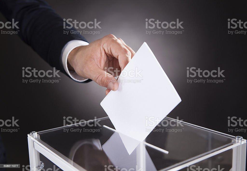 Businessman Inserting Ballot In Box On Desk stock photo