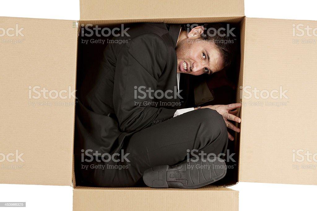 Businessman inside a cardboard box stock photo
