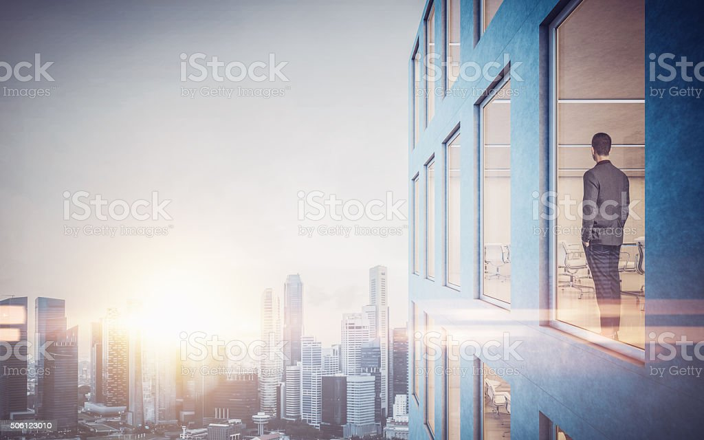 Businessman inside skyscraper, lookng at the city through  window. Horizontal stock photo