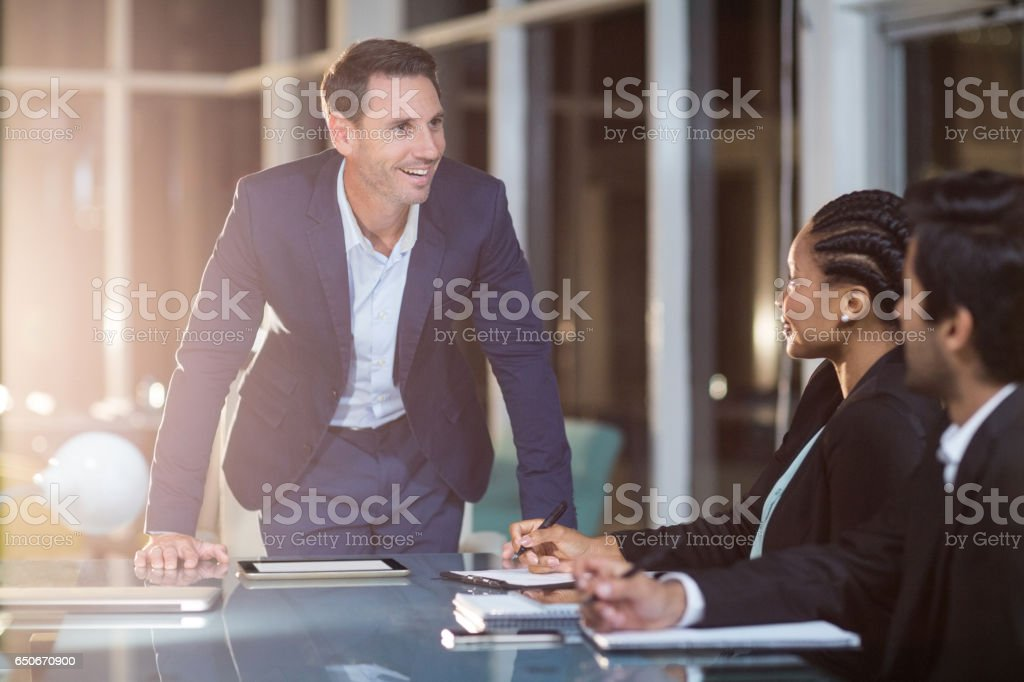 Businessman interacting with coworkers in a meeting in the conference room stock photo